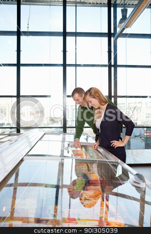 Frozen Goods in Grocery Store stock photo, Smiling man and woman looking at a display in a grocery store by Tyler Olson