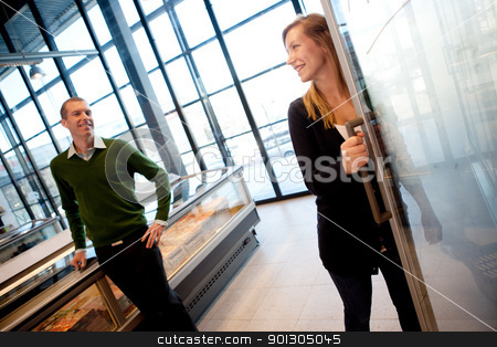 Happy Couple in Supermarket stock photo, A couple smiling at eachother in a supermarket, shallow depth of field, focus on woman. by Tyler Olson