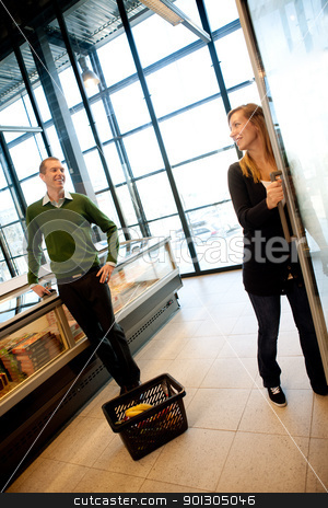 Flirting Couple in Supermarket stock photo, A man and woman smiling at eachother in a trendy supermarket by Tyler Olson