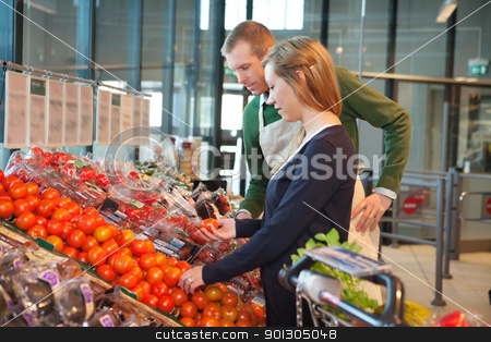 Woman buying tomatoes while standing with shopworker stock photo, Woman holding tomato while standing with shop worker in grocery store by Tyler Olson