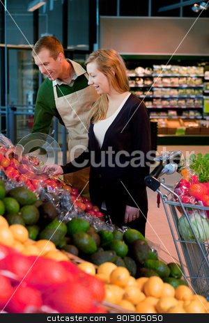 Woman in Supermarket stock photo, A woman buying groceries in a supermarket receiving help from a shop assistant by Tyler Olson