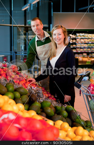Supermarket stock photo, A woman buying fruit and vegetables at a supermarket, receiving help from a grocer by Tyler Olson
