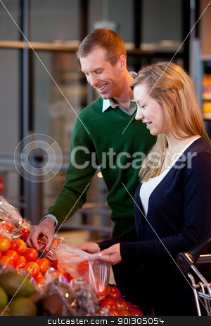 Supermarket Couple stock photo, A happy couple buying fruit in a supermarket - shallow depth of field with sharp focus on woman by Tyler Olson