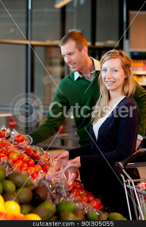 Portrait of Couple in Supermarket stock photo, A happy couple buying fruit and vegetables in a supermarket by Tyler Olson
