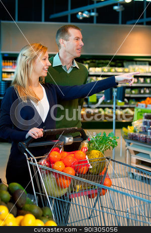 Couple Buying Groceries stock photo, A happy couple in a supermarket buying groceries by Tyler Olson