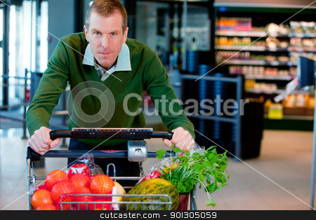 Portrait of a Man in Supermarket stock photo, Portrait of a man pushing a grocery cart in a supermarket by Tyler Olson
