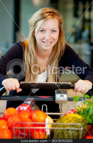 Woman with Fresh Produce stock photo, A happy shopping woman with grocery cart full of fruits and vegetables by Tyler Olson
