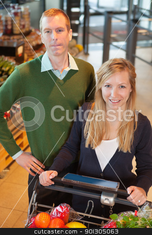 Happy Couple Buying Groceries stock photo, High angle view of smiling woman looking at camera while shopping with man in store by Tyler Olson