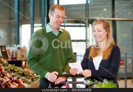 Grocery List stock photo, A happy couple with a shopping cart and grocery list in a supermarket by Tyler Olson