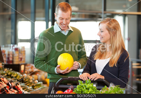 Man and Woman Buying Fruit stock photo, Smiling mid adult man holding fruit while standing with woman in shopping store by Tyler Olson