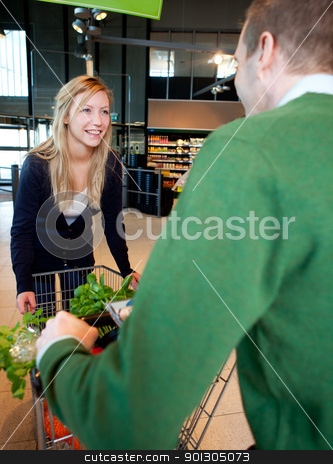 Playful Supermarket Couple stock photo, A woman riding on a grocery cart being pushed by a man by Tyler Olson