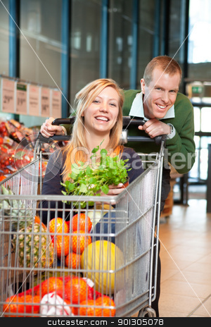 Portrait of playful couple in shopping store stock photo, Mid adult man in playful mood holding shopping cart while woman sitting in it and looking at camera by Tyler Olson