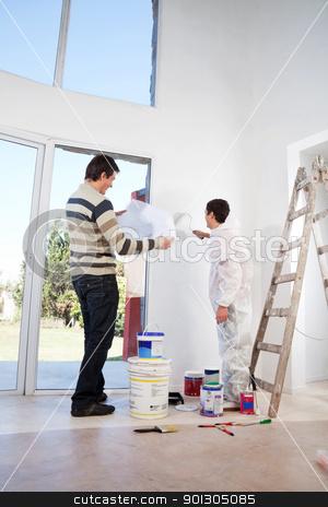 Man going through house plan stock photo, Man going through house plan while painter painting the wall by Tyler Olson