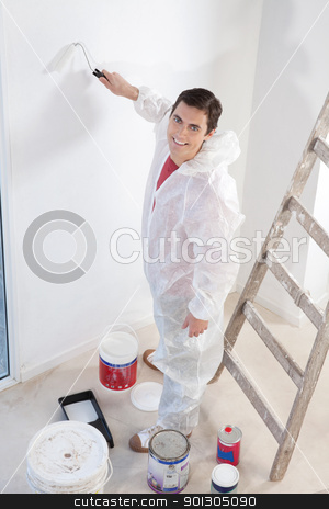 Smiling workman painting the wall with a roller stock photo, Portrait of an smiling workman painting the wall with a roller by Tyler Olson