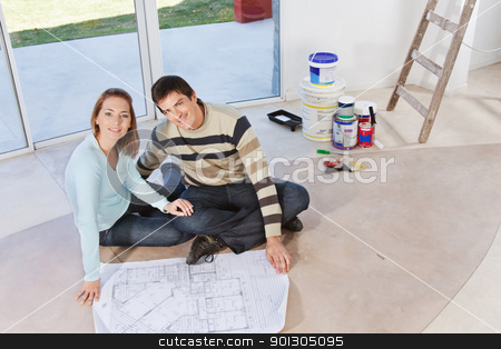 Portrait of smiling couple stock photo, Happy young couple sitting together with blueprint and color buckets in the background by Tyler Olson