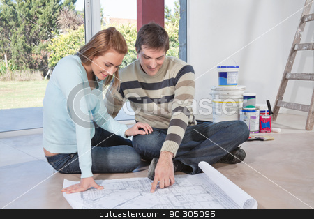 Man showing blueprint of their new house to his wife stock photo, Mature man showing blueprint of their new house to his wife by Tyler Olson