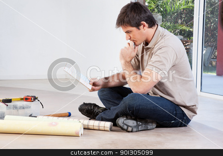 Man sitting on floor and going through color swatch stock photo, Mature man going through the color swatch while sitting on the floor by Tyler Olson