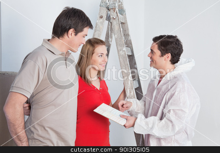 Workman suggesting colors to a mature couple stock photo, Workman suggesting colors to a couple for their new apartment by Tyler Olson