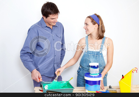 Happy mature couple with painting tools stock photo, Happy mature couple with roller, paint and bucket on table at their new apartment by Tyler Olson