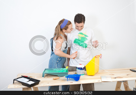 Wife painting on t-shirt stock photo, Young wife painting on t-shirt of husband by Tyler Olson