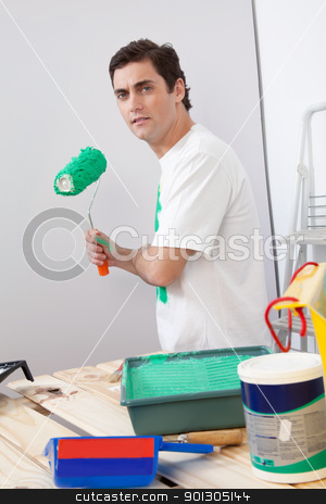 Casual man holding a roller paint brush stock photo, Portrait of casual man holding a roller paint brush in his hand by Tyler Olson