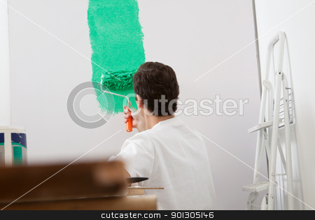 Man painting the wall with a roller stock photo, Rear view of man painting the wall with a roller of new apartment by Tyler Olson