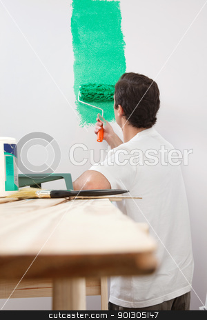 Man paining house with roller stock photo, Rear view of man painting his house with color roller by Tyler Olson