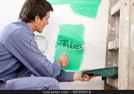 Mature man painting the wall with a roller stock photo, Mature man painting the wall with a roller while holding a paint can by Tyler Olson