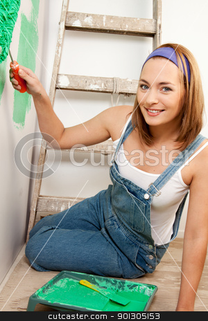 Woman Painting Wall stock photo, Portrait of a woman painting the wall green with a roller brush by Tyler Olson