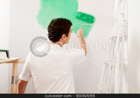 Faceless Painter stock photo, A faceless male painting a wall with a roller brush, home improvements by Tyler Olson