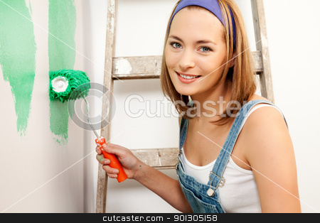 Painting Woman stock photo, A woman with a roller brush, paiting the wall doing home improvements by Tyler Olson