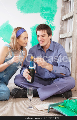 Couple sitting on floor and having champagne stock photo, Couple sitting on floor and having champagne at their new apartment by Tyler Olson