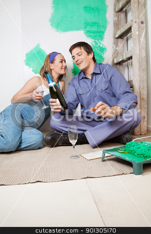 Home Improvement Celebration stock photo, Happy couple sitting on floor and having champagne by Tyler Olson