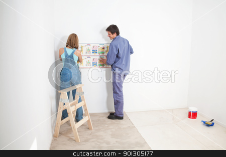 Wallpaper Baby Room stock photo, Couple putting up wall papper in baby room by Tyler Olson