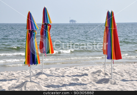 Abandoned Beach and Oil Rig stock photo, Abandoned beach with closed umbrellas.  Off shore oil rig in background. by Danny Hooks