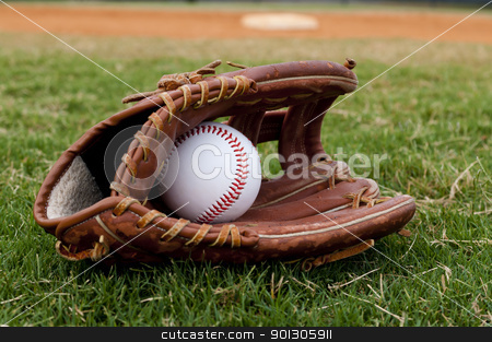 Baseball in Old Glove on Field stock photo, Baseball in old glove on field with base and outfield in background. by Danny Hooks