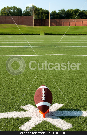 American Football Kickoff stock photo, American football on tee on field with goal post in background. by Danny Hooks