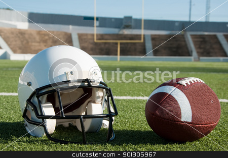 American Football and Helmet on Field stock photo, American football and helmet on field with goal post in background. by Danny Hooks