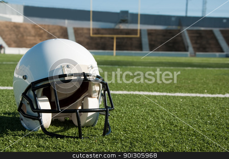 American Football  Helmet on Field stock photo, American football  helmet on field with goal post in background. by Danny Hooks