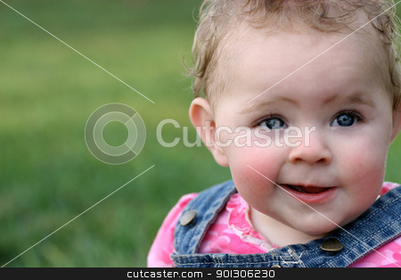 Quirky little girl's grin stock photo, Baby girl with quirky grin in pink and blue with green grass in background by Jonalynn Hansen