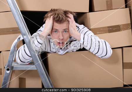 Man surrounded by stacks of cardboards stock photo, Man surrounded by stacks of cardboards by photography33