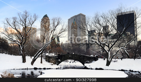 New York City Manhattan Central Park panorama at dusk stock photo, New York City Manhattan Central Park panorama in winter with snow, bridge; freezing lake and skyscrapers at dusk. by rabbit75_cut