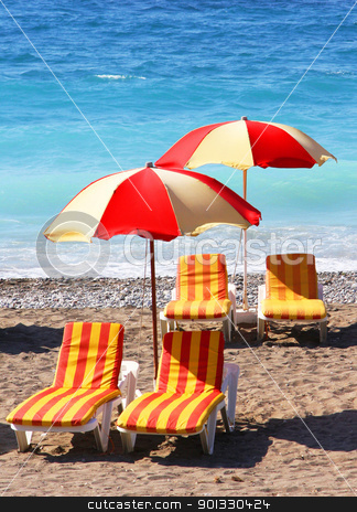 Beach chairs and umbrellas on a sand beach stock photo, Beach chairs and umbrellas on a sand beach in Rhodes island, Greece. by Georgios Kollidas