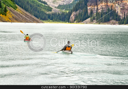 Canoeing on the magnificent Lake Louis  stock photo, Paddling in a canoe on the beautiful turquoise colored Lake Louis against the backdrop of the majestic mountains of the Canadian Rockies partially covered with fog by derejeb
