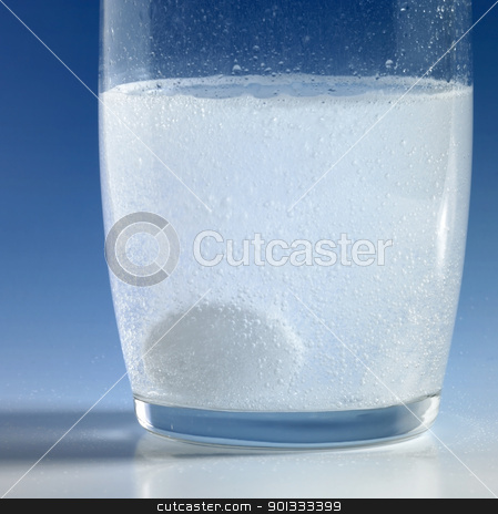 fizzy tablet in a glass of water stock photo, dissolving fizzy tablet floating in a glass of water. Studio photography in blue back by prill