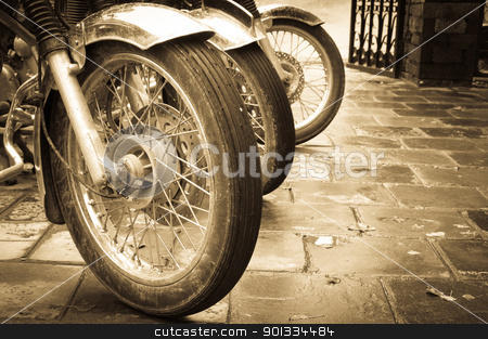 Bikes in a row stock photo, Line of the muddy bikes whells in sepia by Iryna Rasko