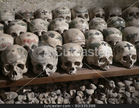 lots of old bones and skulls stock photo, eerie scenery with a pile of old bones and skulls with paintings on them at the Gebeinhaus in Hallstatt (Austria) by prill