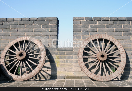 Ancient carriage wheel stock photo, Ancient carriage wheel against brick wall by John Young