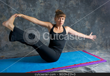 young woman doing yoga posture Navasana or The Boat Pose  stock photo, A brown haired caucasian woman is doing yoga exercise, Navasana Pose or Rotated Boat posture  on yoga mat in studio with mottled background. by Stephen Orsillo
