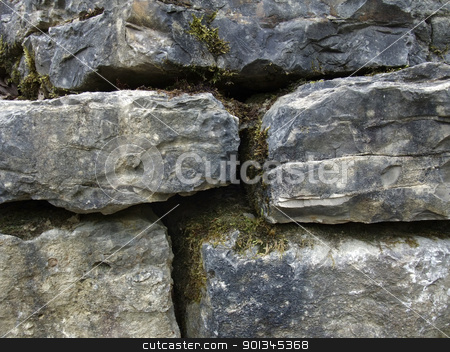 mossy stone wall detail stock photo, full frame detail of a old stone wall with mossy chinks by prill